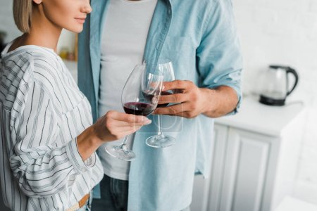 cropped image of young couple clinking with wineglasses in kitchen