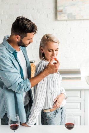 Photo for Handsome boyfriend feeding girlfriend with cherry tomato in kitchen - Royalty Free Image