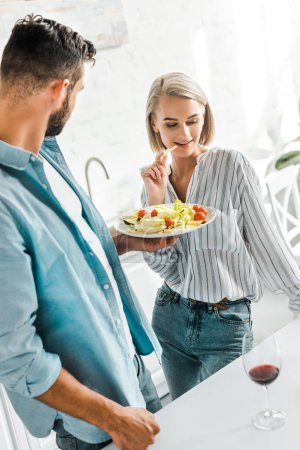 Photo for Attractive girlfriend eating fresh salad from plate in kitchen - Royalty Free Image