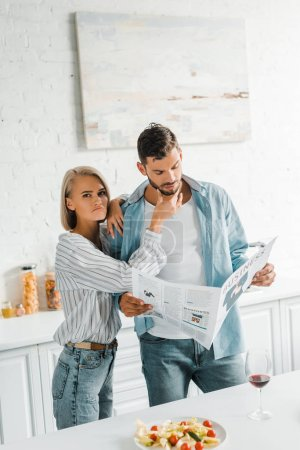 boyfriend reading newspaper and grimacing girlfriend touching his chin in kitchen