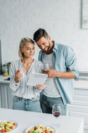 Photo for Smiling young couple looking at tablet in kitchen - Royalty Free Image
