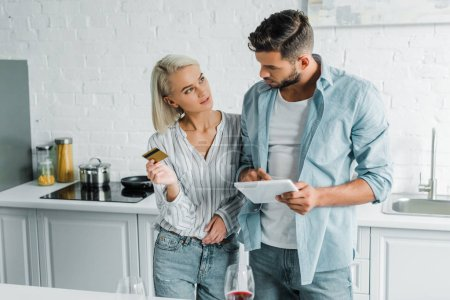 boyfriend holding tablet and girlfriend standing with credit card in kitchen