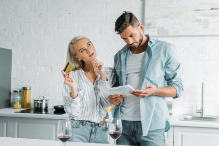 boyfriend holding tablet and pensive girlfriend standing with credit card in kitchen