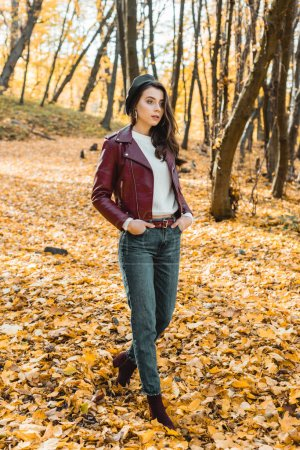 fashionable young woman in beret and leather jacket walking in autumnal park