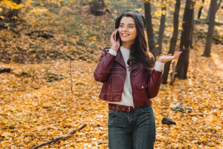 young stylish woman  in leather jacket talking on smartphone and gesturing by hand in autumnal park