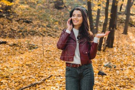 jeune femme élégante en blouson de cuir parler sur smartphone et gesticulant à la main dans le parc automnal