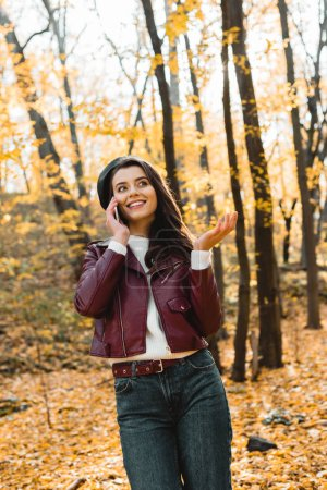 low angle view of happy girl in leather jacket talking on smartphone and gesturing by hand in autumnal park