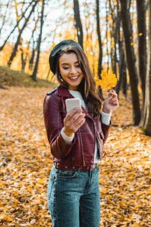 smiling stylish girl in leather jacket taking selfie with yellow leaf on smartphone outdoors