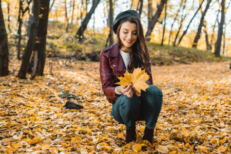 happy stylish girl in beret and leather jacket sitting with yellow in autumnal forest