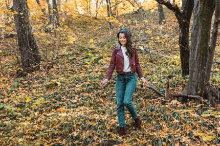 Photo for Fashionable young woman in leather jacket and beret walking down in autumnal park - Royalty Free Image