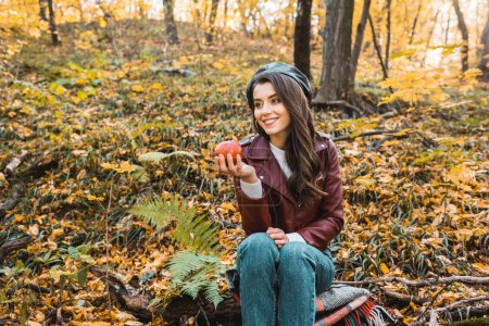 smiling stylish girl in leather jacket sitting on blanket and holding red apple in forest