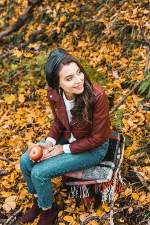 Photo for High angle view of fashionable young woman in beret and leather jacket holding apple outdoors - Royalty Free Image