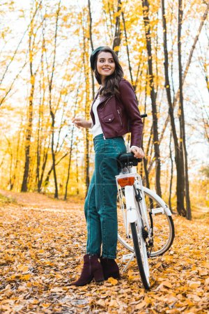 low angle view of happy female model in beret and leather jacket posing near bicycle in autumnal forest