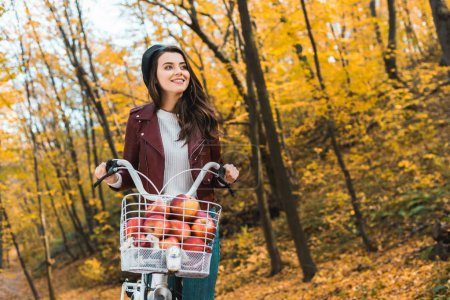 happy fashionable girl in leather jacket carrying bicycle with basket full of red apples in autumnal park