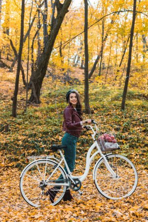 happy fashionable woman in stylish leather jacket and beret carrying bicycle in forest
