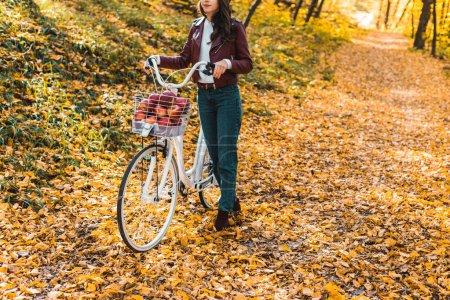 Photo pour Vue partielle de la jeune fille en veste en cuir élégants et béret transportant le vélo dans la forêt automnale jaune - image libre de droit
