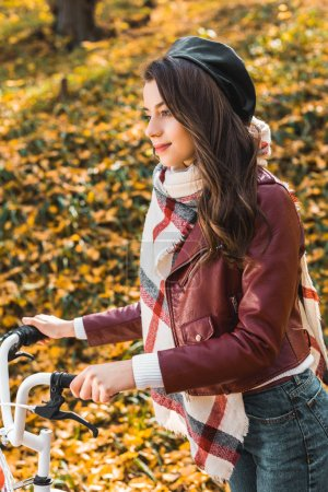 selective focus of cheerful woman in stylish leather jacket and beret carrying bicycle outdoors