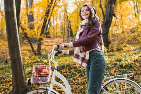 low angle view of fashionable girl in leather jacket and beret carrying bicycle in forest