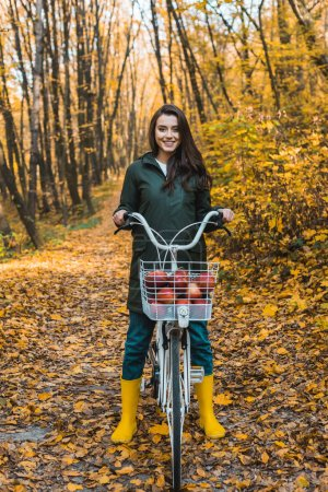attractive smiling girl riding on bicycle with basket full of apples in autumnal forest