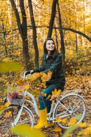 happy young woman riding on bicycle with basket full of apples in autumnal forest