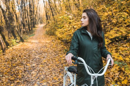 Photo for Selective focus of beautiful young woman carrying bicycle in yellow autumnal forest - Royalty Free Image
