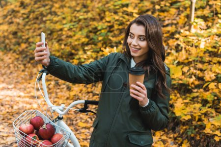 Photo for Cheerful beautiful woman with disposable coffee cup taking selfie on smartphone in autumnal forest - Royalty Free Image