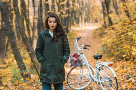 beautiful young woman walking near bicycle in autumnal forest