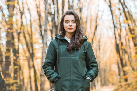beautiful young woman in jacket looking at camera in autumnal forest
