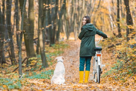 smiling woman with bicycle and her golden retriever sitting near on yellow leafy path in forest