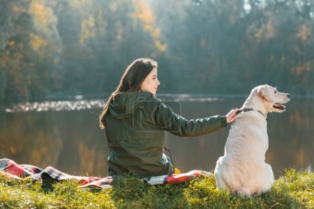 rear view of young woman siting on blanket with adorable golden retriever near pond in park