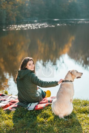 smiling young woman siting on blanket with adorable golden retriever near pond in park