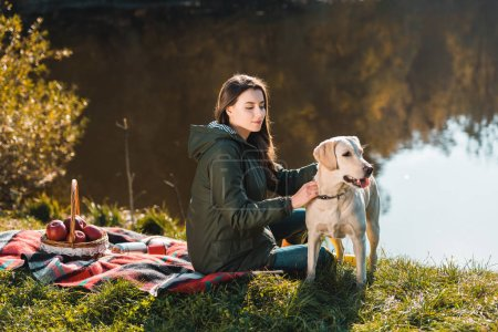 young woman siting on blanket with adorable golden retriever near pond in park