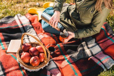 Photo for Partial view of woman pouring coffee from thermos into cup while sitting on blanket with basket full of apples outdoors - Royalty Free Image