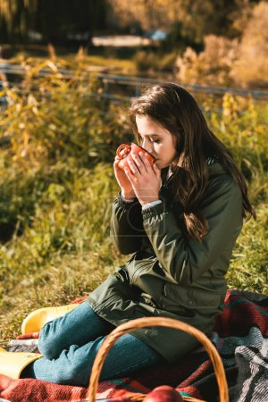 selective focus of beautiful girl drinking coffee outdoors