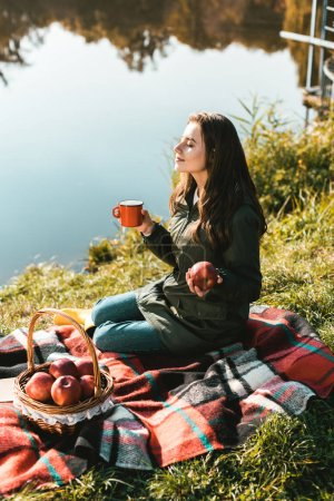 cheerful girl with apple and cup of coffee sitting on blanket near pond