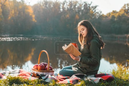 beautiful young woman with coffee cup reading book on blanket near pond in park