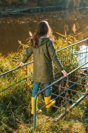 rear view of woman in jacket and yellow rubber boots posing near pond in park