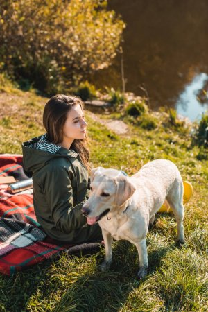 side view of cheerful young woman sitting on blanket with dog outdoors