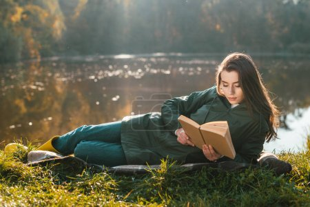 attractive young woman reading book while laying on blanket near pond in park