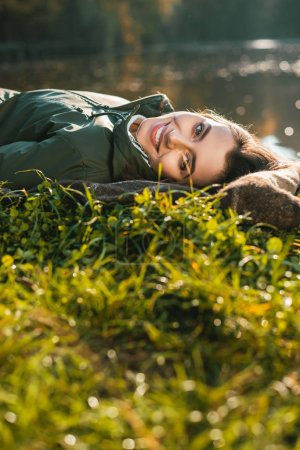 selective focus of smiling woman in laying on blanket and looking at camera outdoors