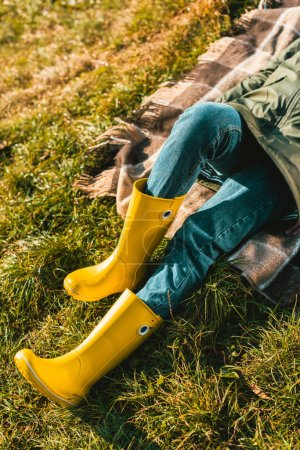 cropped image of woman in yellow rubber boots laying on blanket outdoors