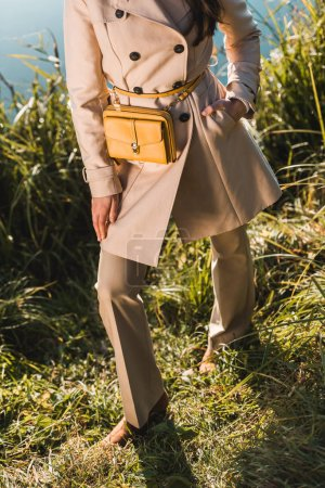 cropped image of fashionable woman in trench coat posing with yellow bag outdoors