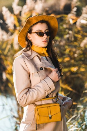 attractive woman in trench coat posing with yellow bag outdoors