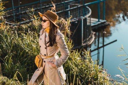 Photo pour Jeune femme attirante en Trench-Coat, lunettes de soleil et chapeau posant près de l'étang dans le parc - image libre de droit