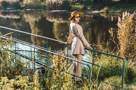 young elegant woman in sunglasses, trench coat and hat posing near pond in park