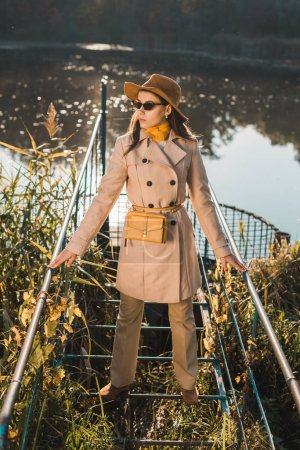 Photo pour Jeune femme à la mode en Trench-Coat, lunettes de soleil et chapeau posant près de l'étang dans le parc - image libre de droit