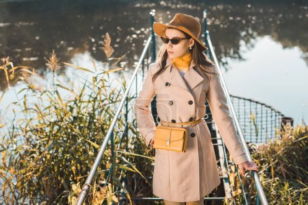 selective focus of fashionable woman in sunglasses, trench coat and hat posing near pond in park