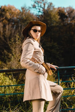 Photo for Selective focus of young attractive woman in hat and sunglasses looking at camera outdoors - Royalty Free Image