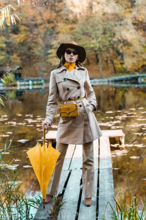 confident stylish woman in sunglasses, trench coat and hat posing with yellow umbrella near pond in park