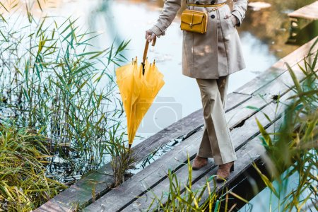 cropped image of fashionable woman in trench coat standing with yellow umbrella near pond